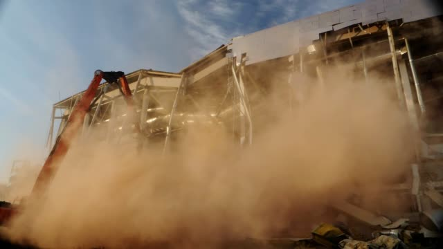 excavator near hockey arena in dust clouds on sunny day