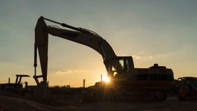 Excavator on New Home Construction Job Site Heavy equipment parked on new home job site time lapse at sunset with lens flare and star burst. construction machinery stock videos & royalty-free footage