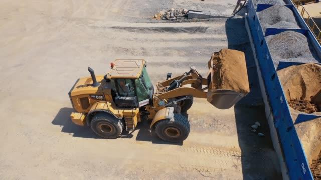 Bидео Excavator on the territory of asphalt manufacture outdoors.