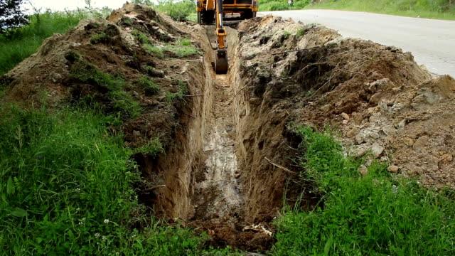 grävmaskin drift och gräva jord för ny elledning. - excavator bildbanksvideor och videomaterial från bakom kulisserna
