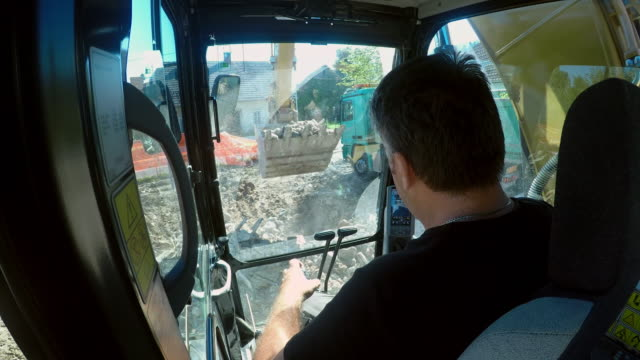 LD Excavator operator moving debris on at the construction site