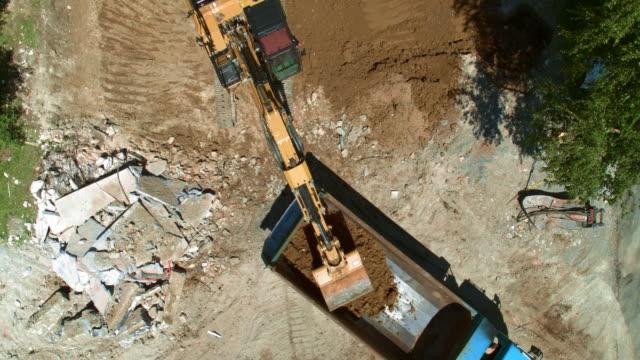 在陽光明媚的建築工地, 航空挖掘機將土壤放在卡車後部 - 起重機 個影片檔及 b 捲影像