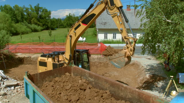 AERIAL Excavator placing soil onto the trailer of a truck Aerial shot of an excavator placing soil dug at the site onto a truck at the sunny building site. Shot in Slovenia. dump truck stock videos & royalty-free footage