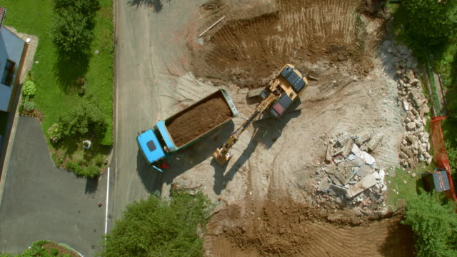 AERIAL Excavator placing the last bucket of soil onto the truck at the building site Aerial shot above the building site where the excavator is placing the last bucket of soil onto the truck. Shot in Slovenia. construction vehicle stock videos & royalty-free footage