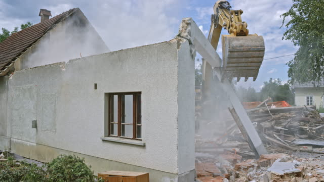 Excavator pushing the last remaining walls of a building and demolishing them video