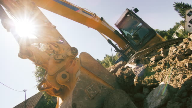 SLO MO Excavator scraping a layer of soil into the bucket at the construction site