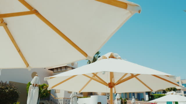 Excellent rest in a luxury hotel. A row of snow-white umbrellas against the blue sky background. Steadicam shot video