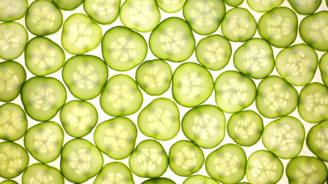 excellent top view of sliced fresh green cucumber in flat lay close up, rotating contra clockwise. - cetriolo video stock e b–roll