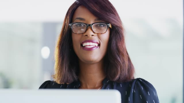 Excelling in my career and so can you! 4k video footage of a young businesswoman using a laptop and showing thumbs up in a modern office representing stock videos & royalty-free footage