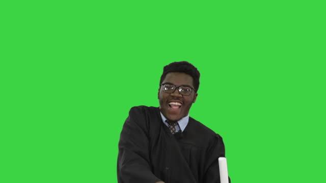 vídeos de stock, filmes e b-roll de animado estudante afro-americano jogando argamassa no ar e fazendo dança boba com seu diploma em uma tela verde, chroma key - beca