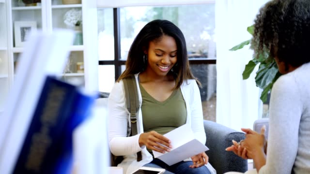 Excited African American teenage girl receives college acceptance letter Happy African American teenage girl shouts with excitement upon reading a college acceptance letter. A female high school guidance counselor hands her the letter. guidance stock videos & royalty-free footage