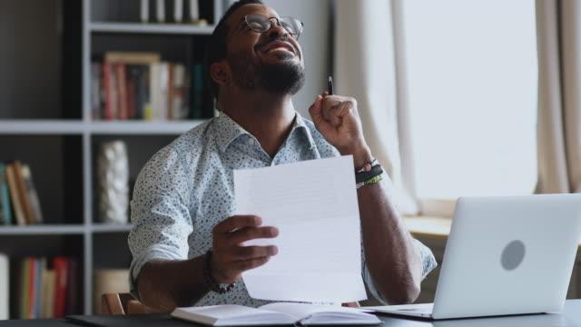 vídeos de stock e filmes b-roll de excited african male student employee read good news in letter - mensagem