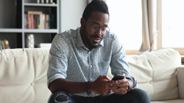 upphetsad afrikansk man hold smartphone känner sig överlycklig om mobil vinna - lotteri bildbanksvideor och videomaterial från bakom kulisserna