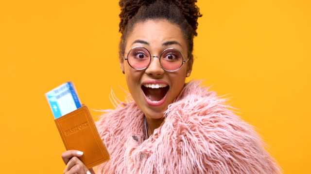Excited african woman showing passport and travel tickets on yellow background Excited african woman showing passport and travel tickets on yellow background passport stock videos & royalty-free footage