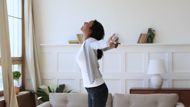vídeos y material grabado en eventos de stock de mujer africana emocionada girando con los brazos extendidos en el nuevo apartamento - propiedad inmobiliaria