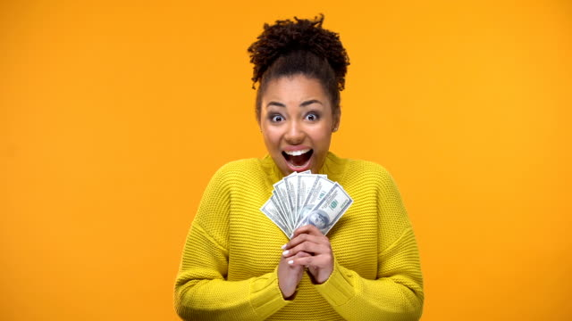 Excited African-American woman holding bunch of dollars, lottery winner, fortune