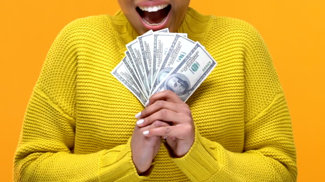Excited afro-american female showing dollars on bright background, investment