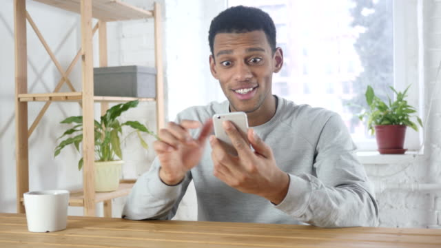 Excited Afro-American Man Celebrating Success while Using Smartphone Excited Afro-American Man Celebrating Success while Using Smartphone ecstatic stock videos & royalty-free footage