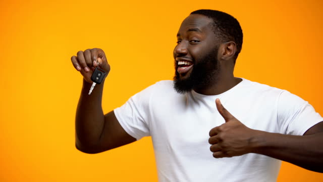 Excited Afro-American man holding car key and showing thumbs up, purchase Excited Afro-American man holding car key and showing thumbs up, purchase car key stock videos & royalty-free footage