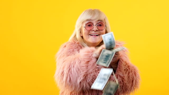 excited aged lady throwing dollar bills around, lottery win financial investment - risparmi video stock e b–roll