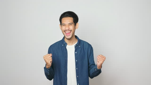 Excited asian man celebrating success while standing over light gray background, Happy asia male wining, reaching achievement, Portrait of  positive gesture and facial expression, 4k resolution
