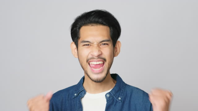 Excited asian man celebrating success while standing over light grey background, Happy asia male wining, reaching achievement, Headshot positive gesture and facial expression, 4k resolution