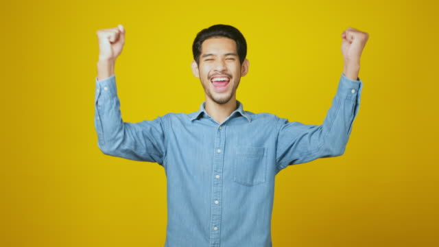 Excited asian man celebrating success while standing over yellow background, Happy asia male wining, reaching achievement, Positive gesture and facial expression, portrait, 4k resolution