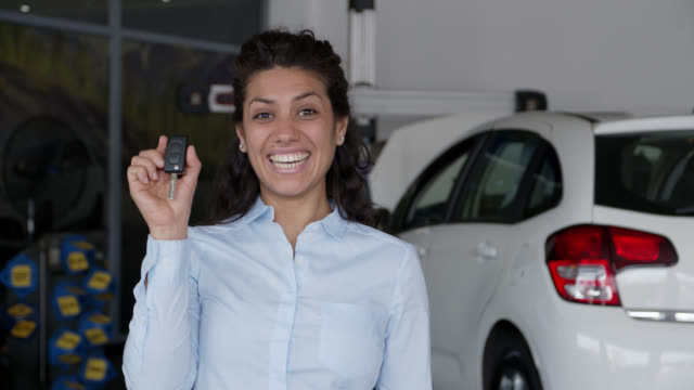 Excited beautiful young woman holding the keys to her new car smiling at camera