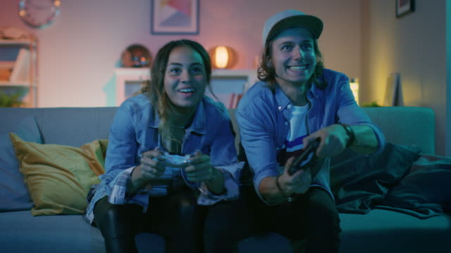 Excited Black Gamer Girl and Young Man Sitting on a Couch and Playing Video Games on Console. They Plays with Wireless Controllers and Give High Five. Cozy Room is Lit with Warm and Neon Light.