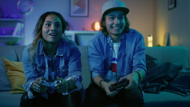 excited black gamer girl and young man sitting on a couch and playing video games on console. they plays with wireless controllers. cozy room is lit with warm and neon light. - gaming filmów i materiałów b-roll