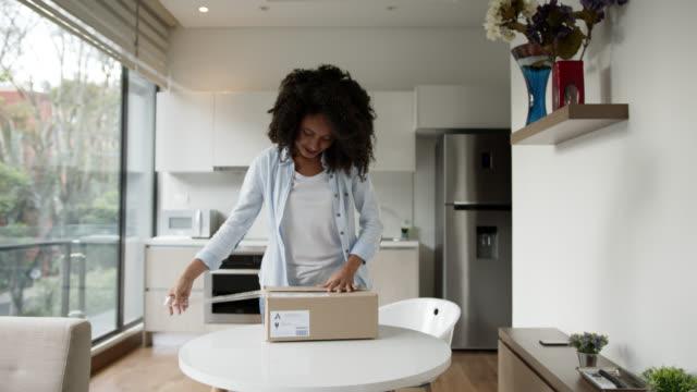 vídeos de stock, filmes e b-roll de mulher negra animada em casa abrindo um pacote e celebrando o que ela recebeu - embrulho