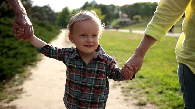 excited boy walking with grandparents in park - grandparents stock videos & royalty-free footage