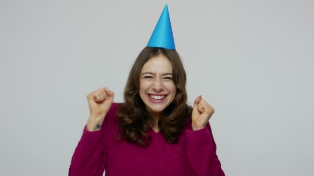 excited brunette woman pointing at funny cone on her head, having fun and dancing, rejoicing at birthday party - 30 34 anni video stock e b–roll