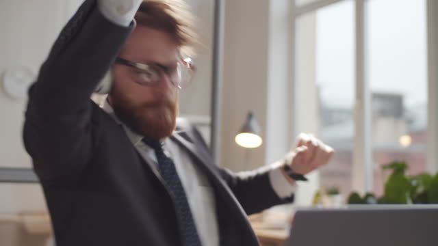 Excited Businessman in Headphones Dancing to Music at Office Desk