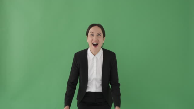 Excited businesswoman covering mouth with hands