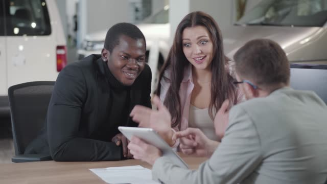 Excited Caucasian woman choosing automobile on salesman's tablet and hugging her African American husband or boyfriend. Successful businessman buying new car for his wife or girlfriend in showroom. Excited Caucasian woman choosing automobile on salesman's tablet and hugging her African American husband or boyfriend. Successful businessman buying new car for his wife or girlfriend in showroom. car salesperson stock videos & royalty-free footage