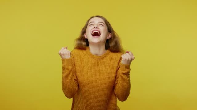возбужденный чемпион. энтузиазм вне себя от радости красивая девушка в пуловер радоваться победе, празднуя успех - блестящий стоковые видео и кадры b-roll