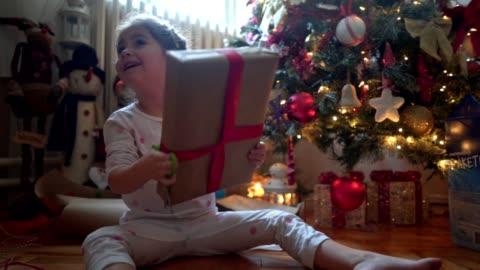 vidéos et rushes de heureux enfant secouant présente avant leur ouverture le matin de noël - cadeau