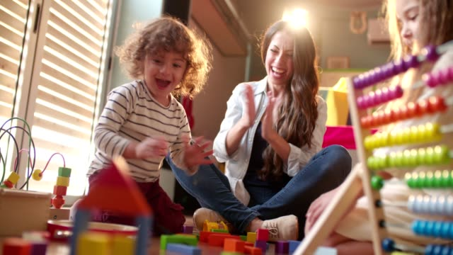Excited children and babysitter playing with toys on the floor Excited boy and girl and their young aunt clapping and playing with toys playroom stock videos & royalty-free footage