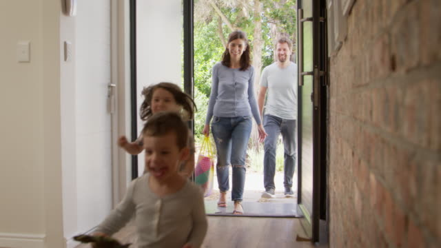 excited children arriving home with parents - edificio residenziale video stock e b–roll