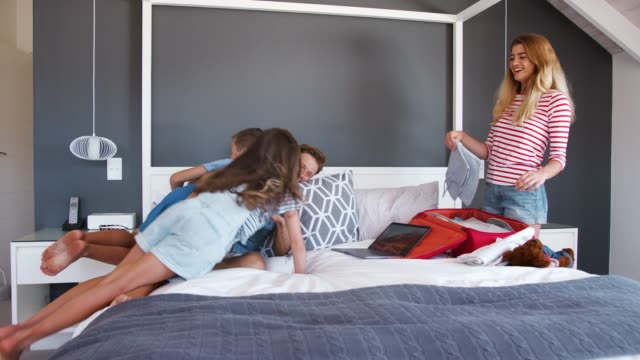excited children jump on bed as parents pack for vacation - fare il solletico video stock e b–roll