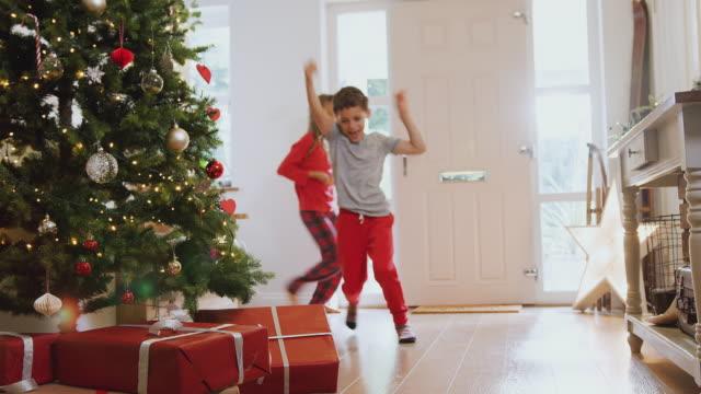 upphetsad barn öppnar presenter av träd på juldagens morgon - christmas present bildbanksvideor och videomaterial från bakom kulisserna