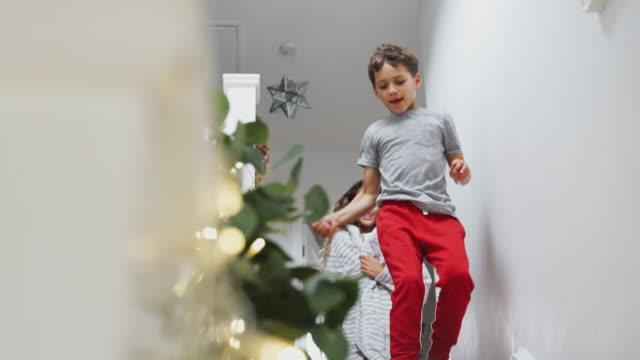 stockvideo's en b-roll-footage met opgewonden kinderen die naar beneden rennen om cadeaus te openen op kerst ochtend - christmas tree