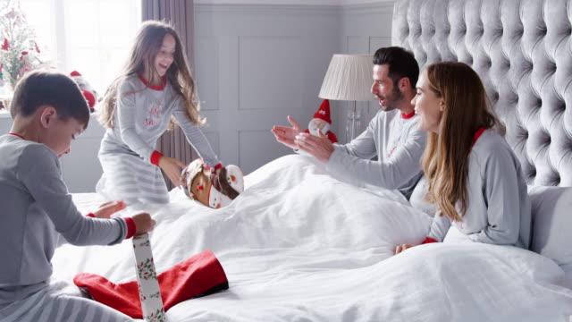 glada barn som springer in i föräldrar sovrum hemma med strumpor som familj öppna presenter på juldagen - christmas gift family bildbanksvideor och videomaterial från bakom kulisserna