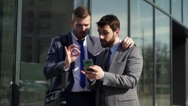 Excited colleague showing a shares raising on a stock market to his coworker