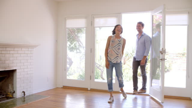 excited couple explore new home on moving day - new home stock videos and b-roll footage