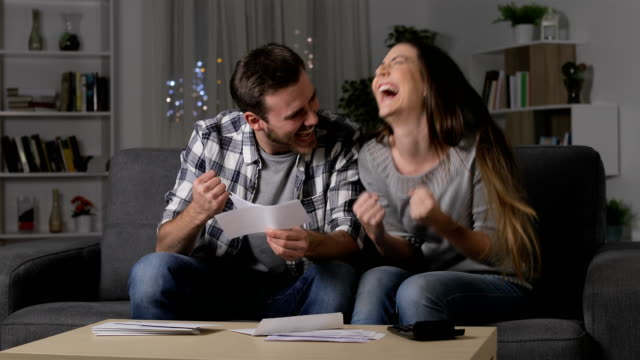 excited couple receiving good news on mail - reso video stock e b–roll