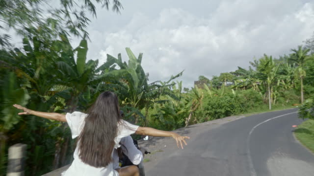 Excited Couple Traveling on Scooter in Tropics video