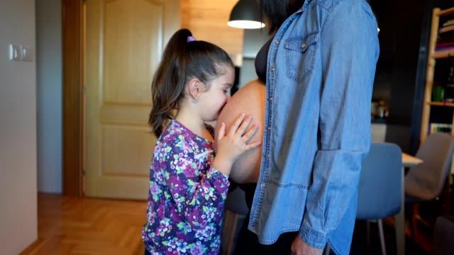 興奮して娘にすぐ生まれの兄弟に彼女を抱きしめる - 兄弟姉妹点の映像素材/bロール
