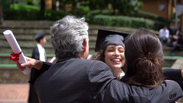 Excited daughter running to celebrate and hug her parents after receiving her degree at colllege